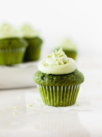 mini matcha cupcake topped with matcha honey frosting with more mini cupcakes in the background.