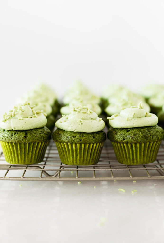 frosted mini matcha cupcakes lined up on a cooling rack.
