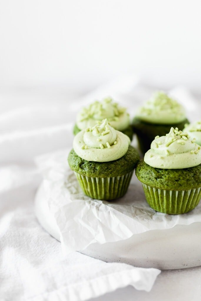 4 mini matcha cupcakes on a white platter covered with white parchment.
