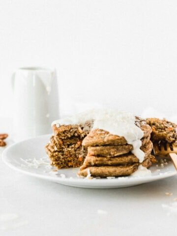 stack of carrot cake pancakes on a white plate with a bite taken out.