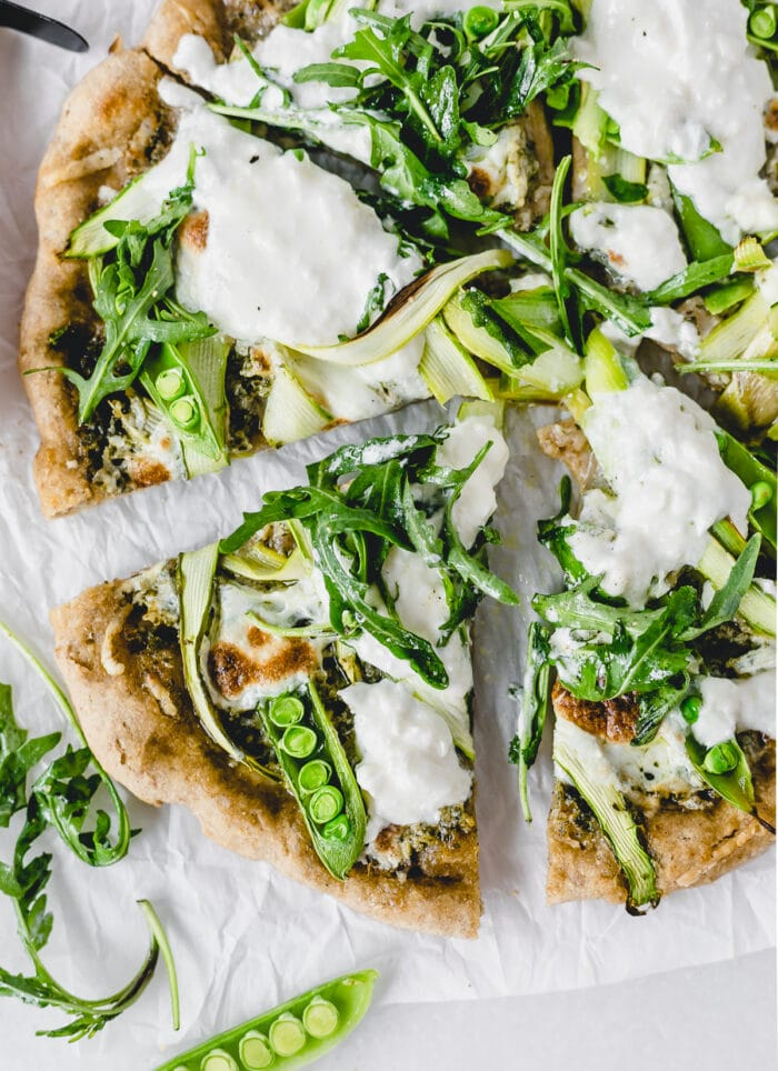 overhead view of sliced asparagus snap pea pizza with burrata and arugula.