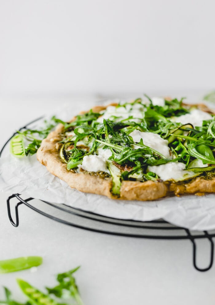 asparagus snap pea pizza with burrata and arugula on a wire cooling rack lined with parchment.