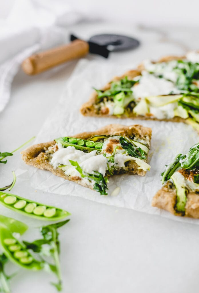 slice of asparagus snap pea pizza with burrata and arugula with a bite taken out.