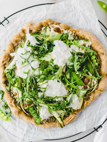 overhead view of asparagus snap pea pizza with burrata and arugula on a wire cooling rack lined with parchment.