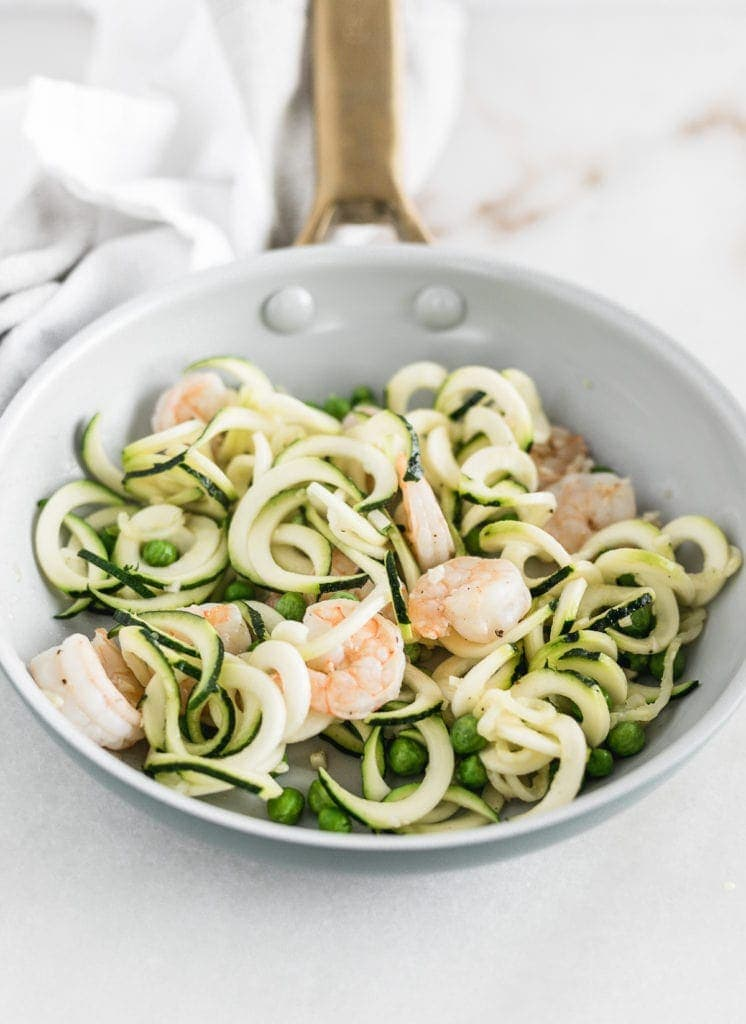 shrimp, peas, and zucchini noodles in a skillet.