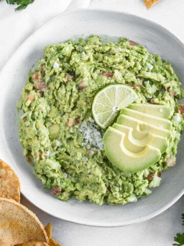 easy homemade guacamole in a bowl with chips around it.