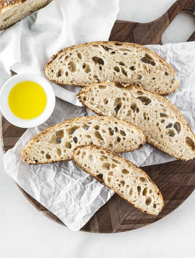 slices of homemade sourdough bread on a round wooden cutting board with a bowl of olive oil.