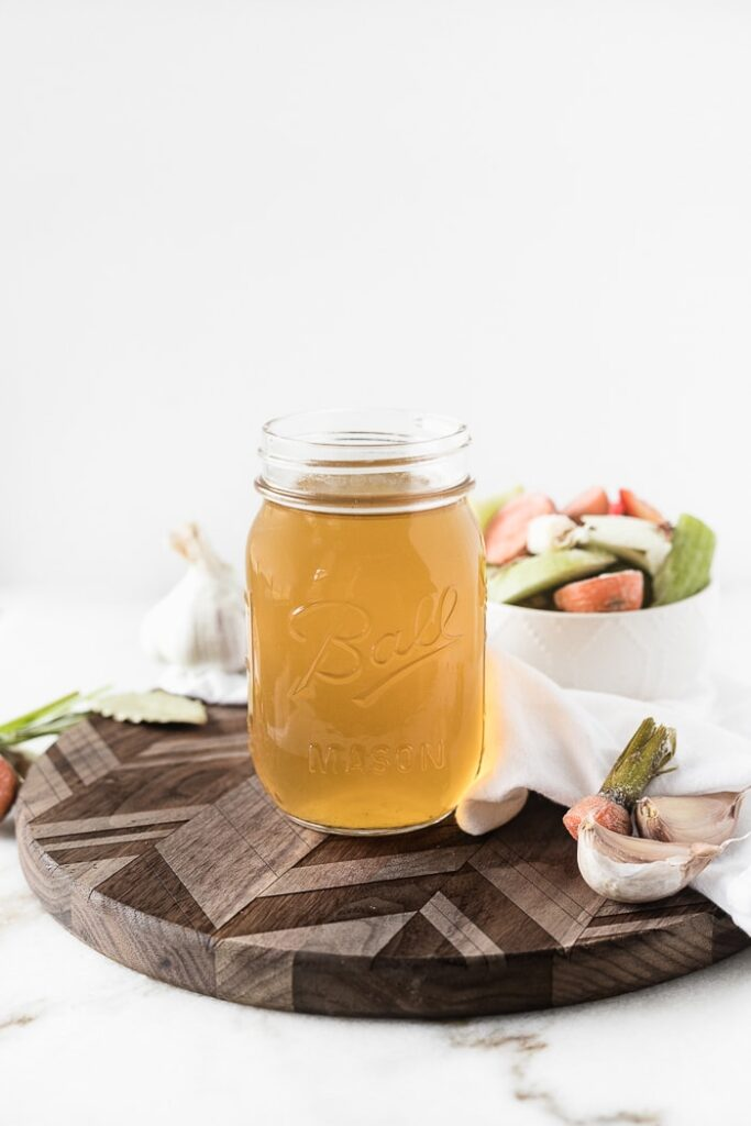 mason jar of bone broth on a wooden cutting board, surrounded by kitchen scraps and a white napkin.