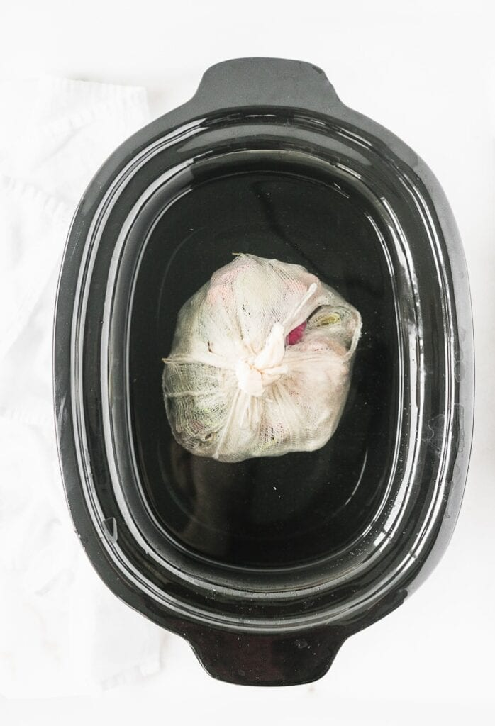 black slow cooker pot with a cheesecloth bundle of vegetables submerged in water for making broth.