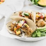 Crunchy coconut fish tacos topped with a fresh mango salsa on a white plate.