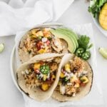 Crunchy coconut fish tacos topped with a fresh mango salsa.