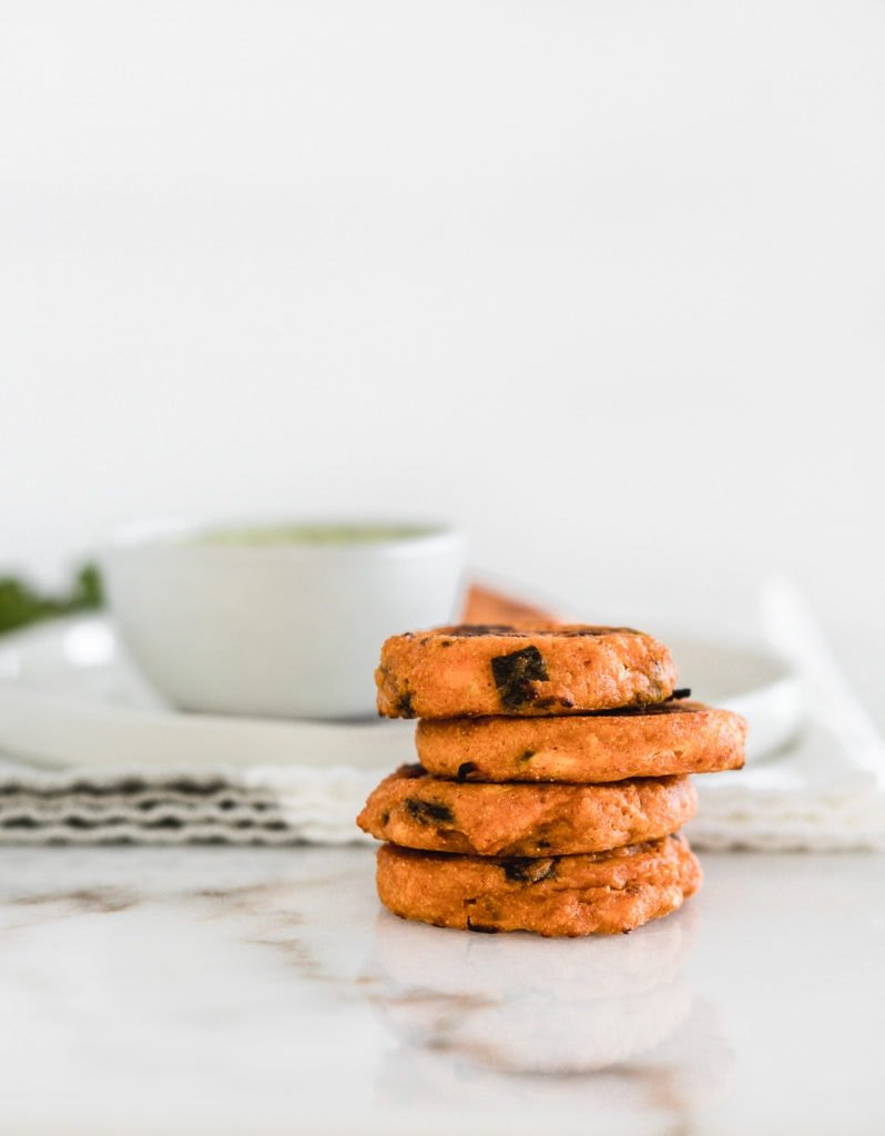 stacked sweet potato cakes with a white bowl of dipping sauce in the background.