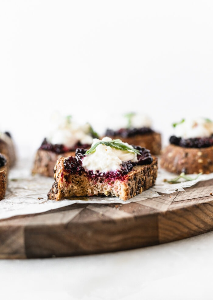 roasted berry burrata bruschetta with a bite taken out on a wooden serving board.
