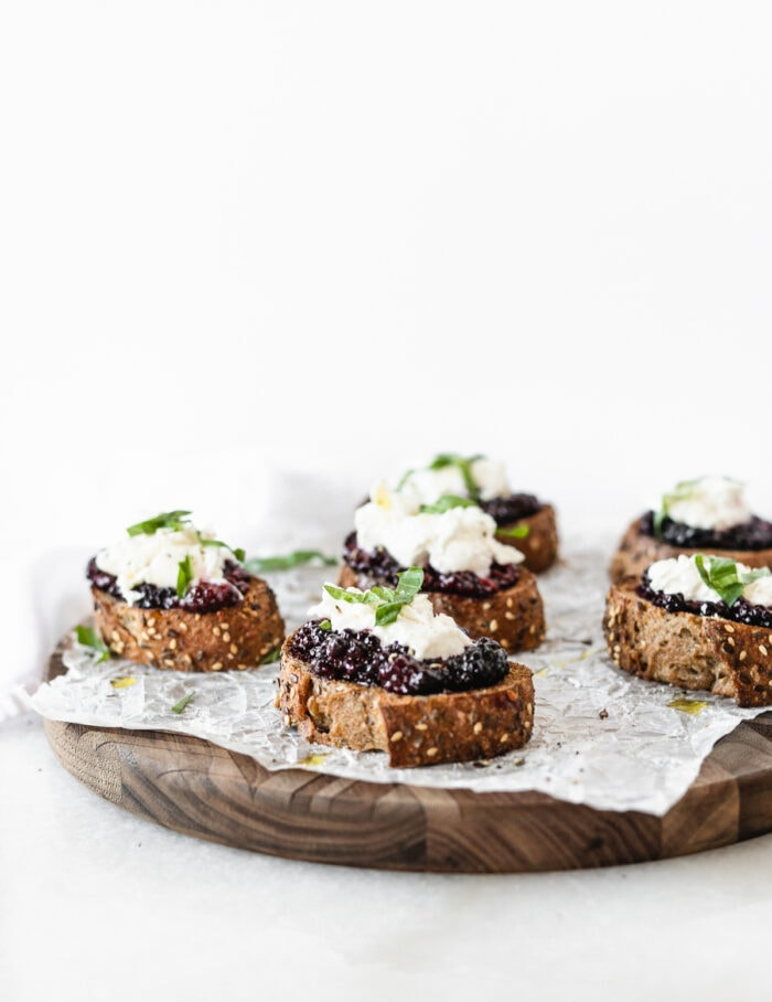 roasted blackberry burrata bruschetta on a wooden serving board covered with parchment.