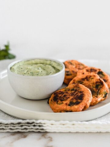 Roasted poblano sweet potato cakes on a plate with a green sauce.