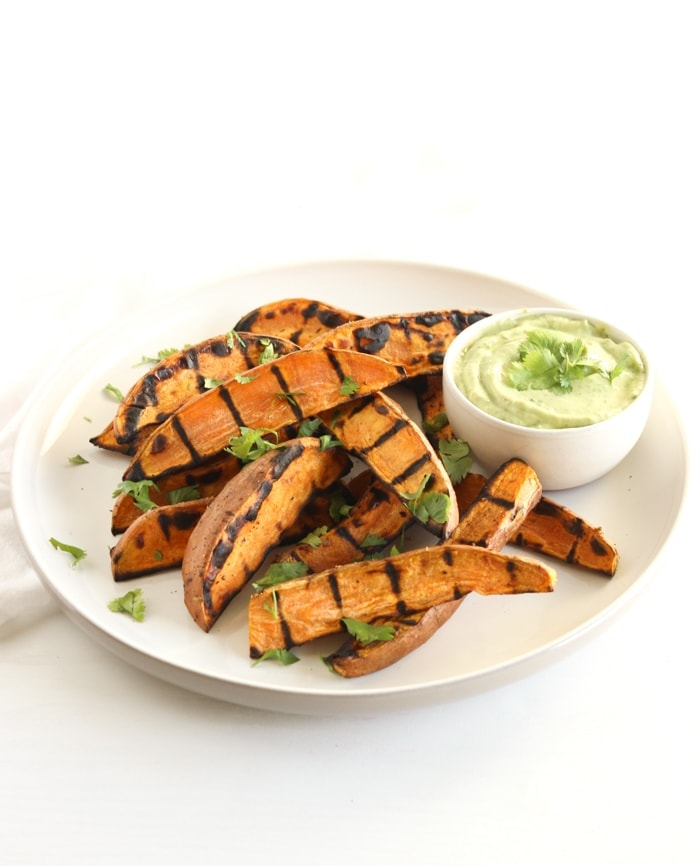 Grilled sweet potato wedges with avocado cream sauce for dipping are the perfect easy, healthy side dish to go with burgers, grilled chicken and more! (vegetarian, gluten-free)