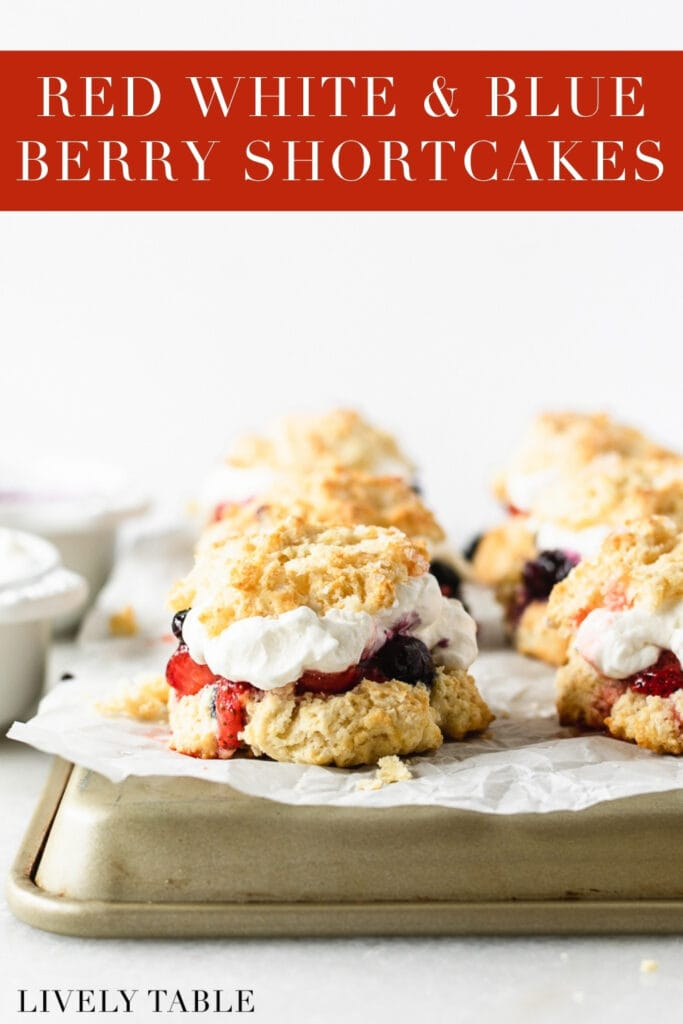 red white and blue berry shortcakes on a parchment lined tray with text overlay.