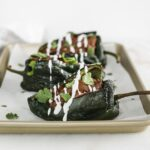 Mole chicken stuffed poblanos topped with cilantro and a white sauce on a baking sheet.