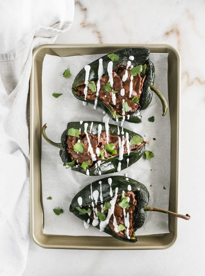 Mole chicken stuffed poblanos on a cooking sheet.