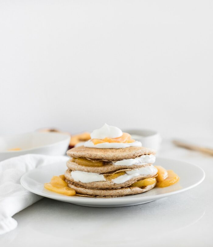 stack of pancakes layered with yogurt and peach compote on a white plate.
