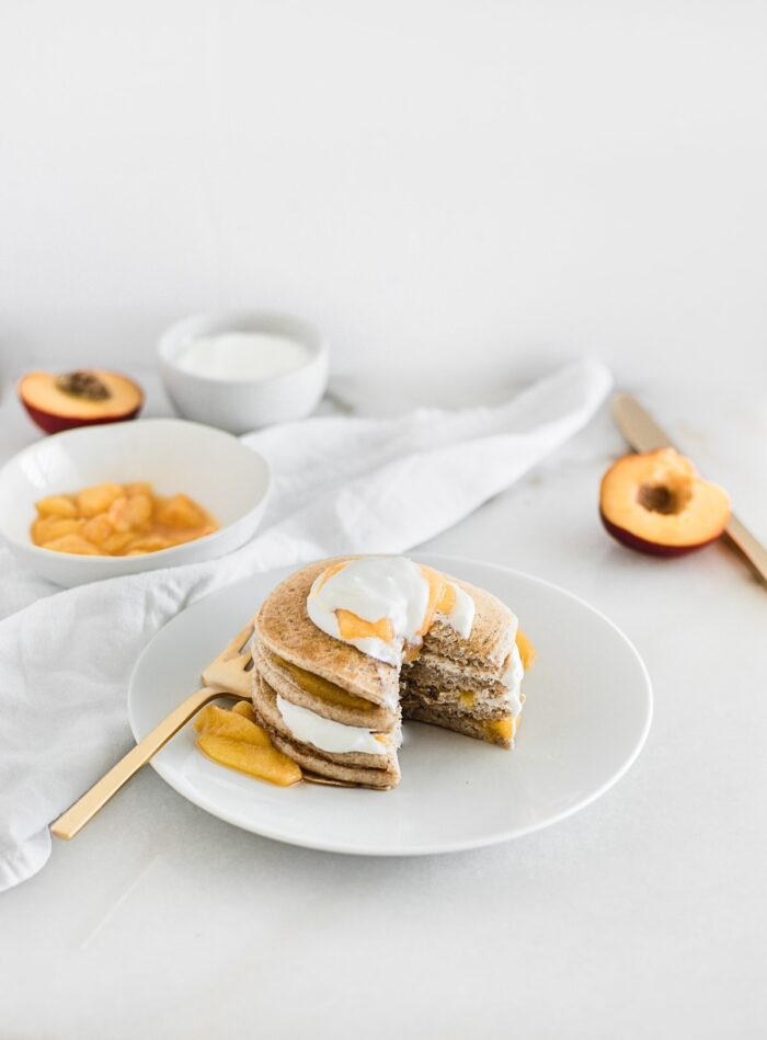healthy peaches and cream pancakes stacked on a white plate with a gold fork next to them and a bite cut out with peach halves and peach compote in a bowl behind them..