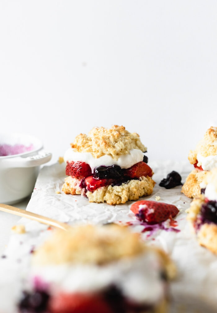 red white and blueberry shortcake on a piece of parchment with stray strawberries and blueberries around it.
