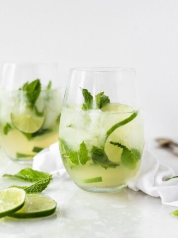 white wine mojito in a stemless wine glass with lime slices and mint around it.