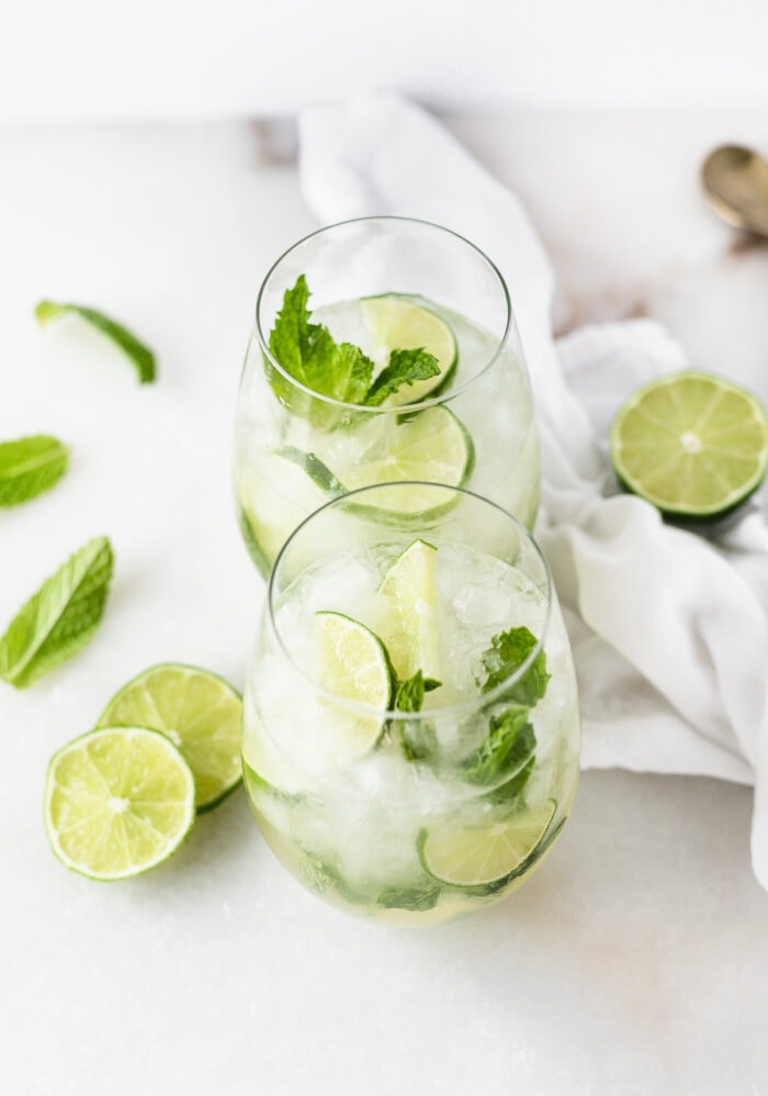 two white wine mojitos in stemless wine glasses surrounded by lime slices and mint.