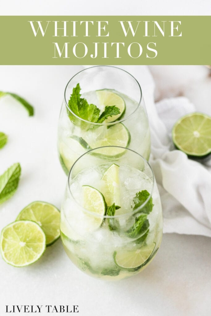 two white wine mojitos in stemless wine glasses surrounded by lime slices and mint with text overlay.