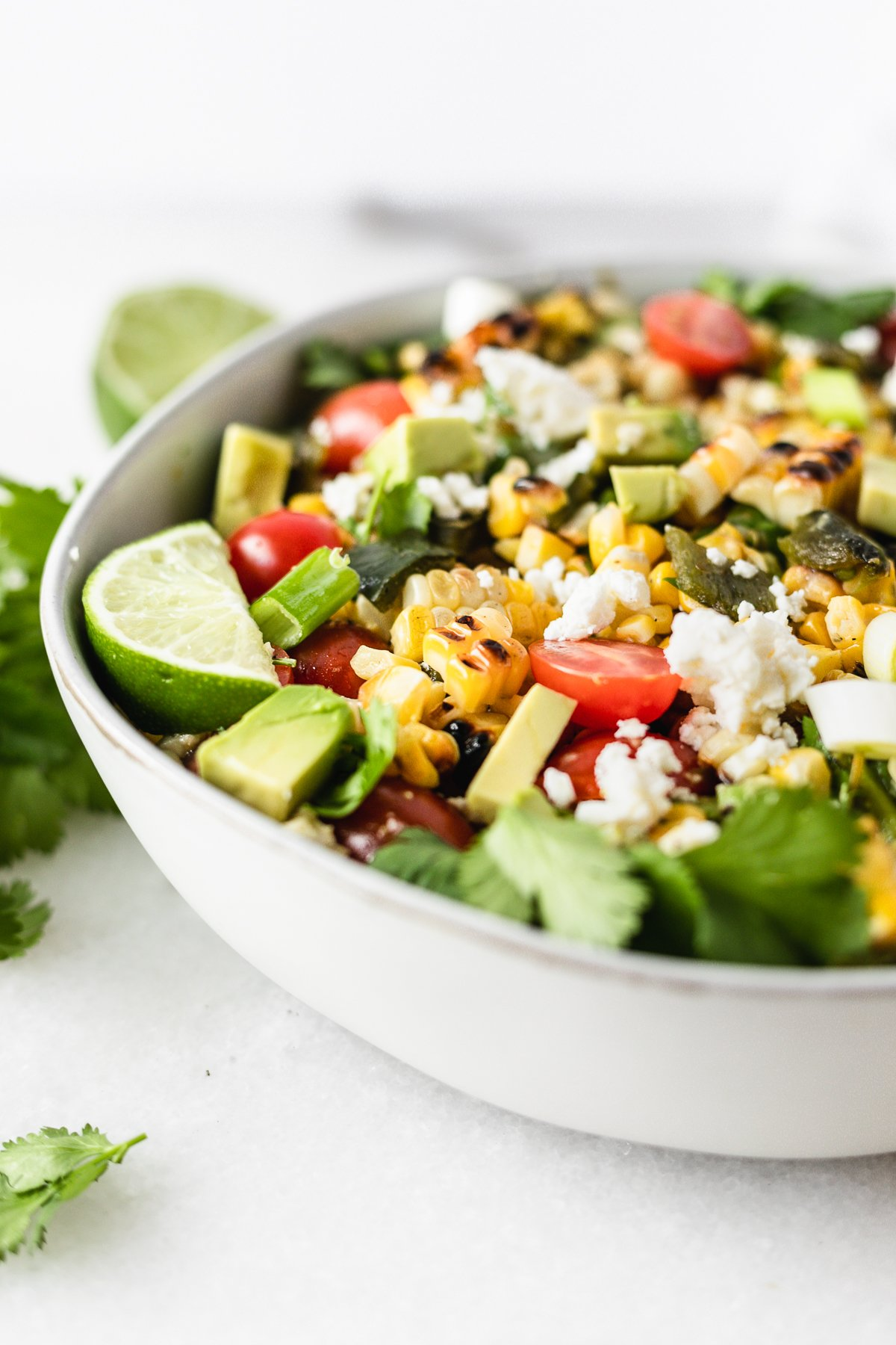 This grilled corn summer salad features grilled fresh corn and poblanos with fresh tomatoes and avocado for a delicious summer salad that's perfect for cookouts! (gluten-free, vegetarian) | via livelytable.com