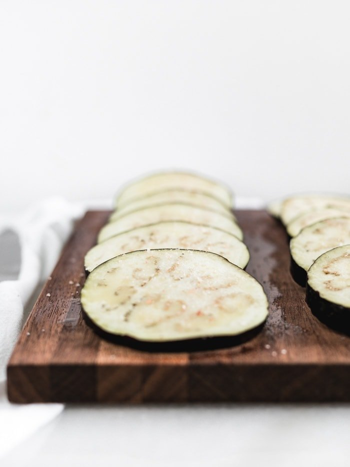 sliced eggplant on a brown cutting board sprinkled with salt