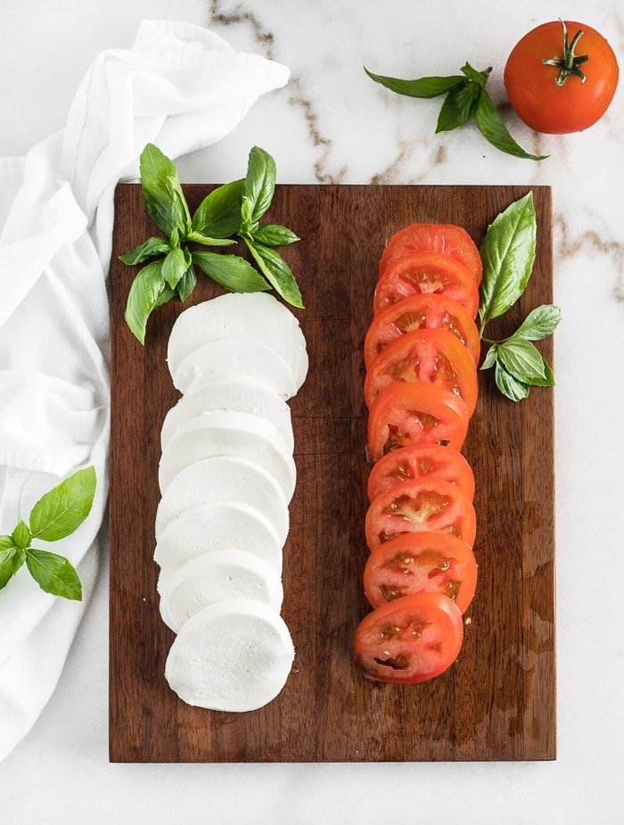 sliced mozzarella cheese, sliced tomatoes, and fresh basil on a cutting board