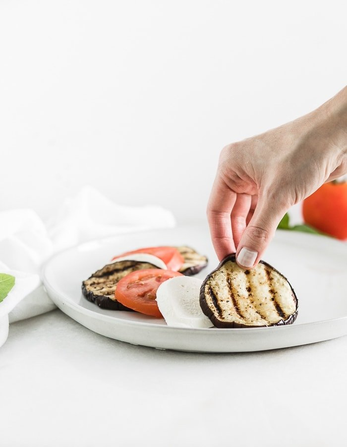 hand placing a slice of grilled eggplant on a plate with layers of sliced tomato and mozzarella