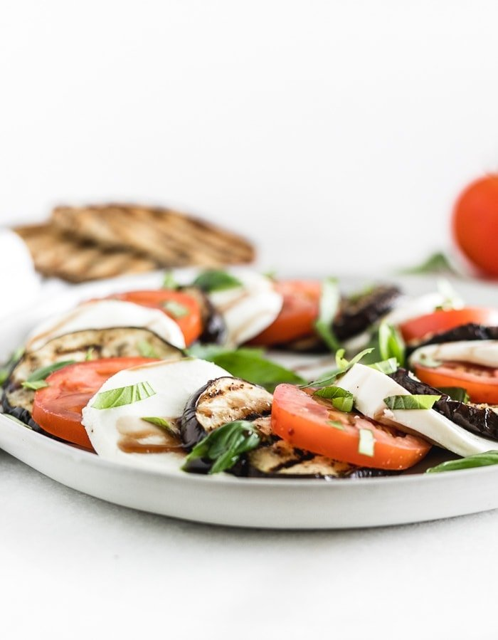 grilled eggplant layered with sliced tomatoes and mozarella with basil and balsamic vinegar on a plate
