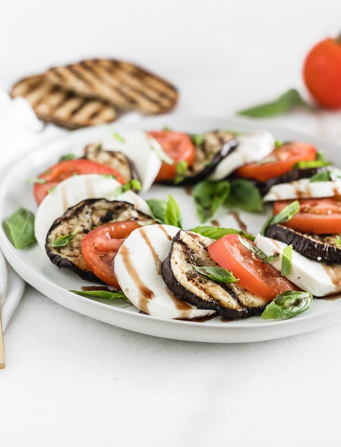 grilled eggplant, tomato and mozarella caprese salad on a grey plate with grilled toast in the background