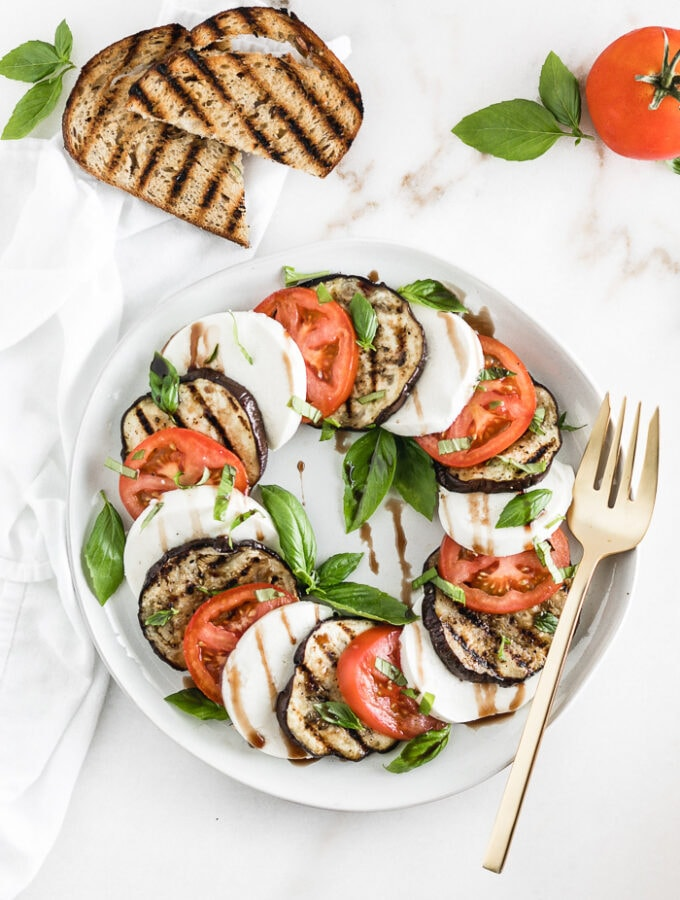 overhead shot of grilled eggplant caprese salad on a plate with a gold fork, surrounded by grilled toast and a tomato.