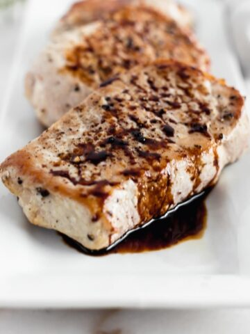 Skillet Pork Chops with Balsamic Glaze on a white square plate.