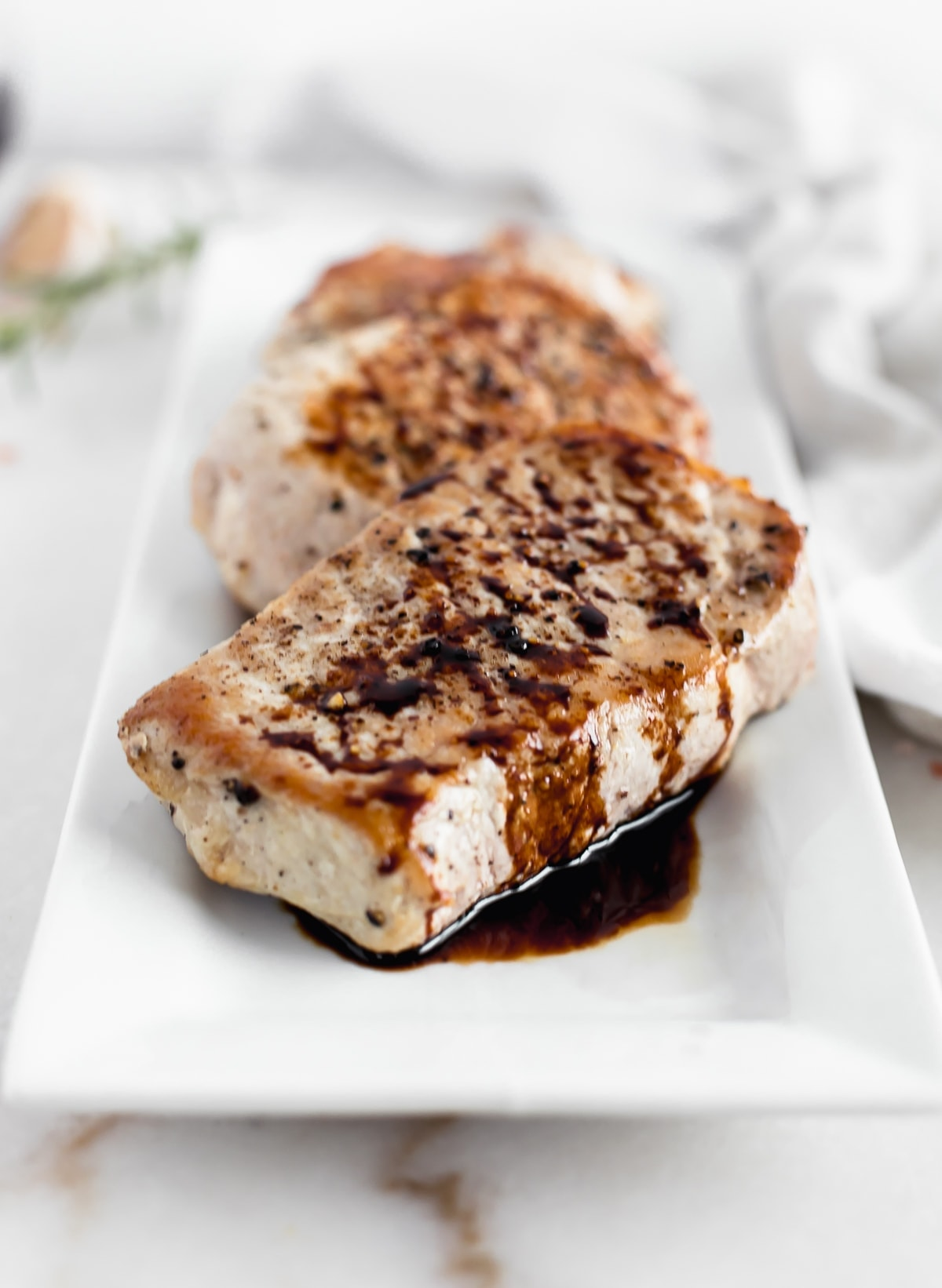 closeup of balsamic skillet pork chops on a white rectangular platter.
