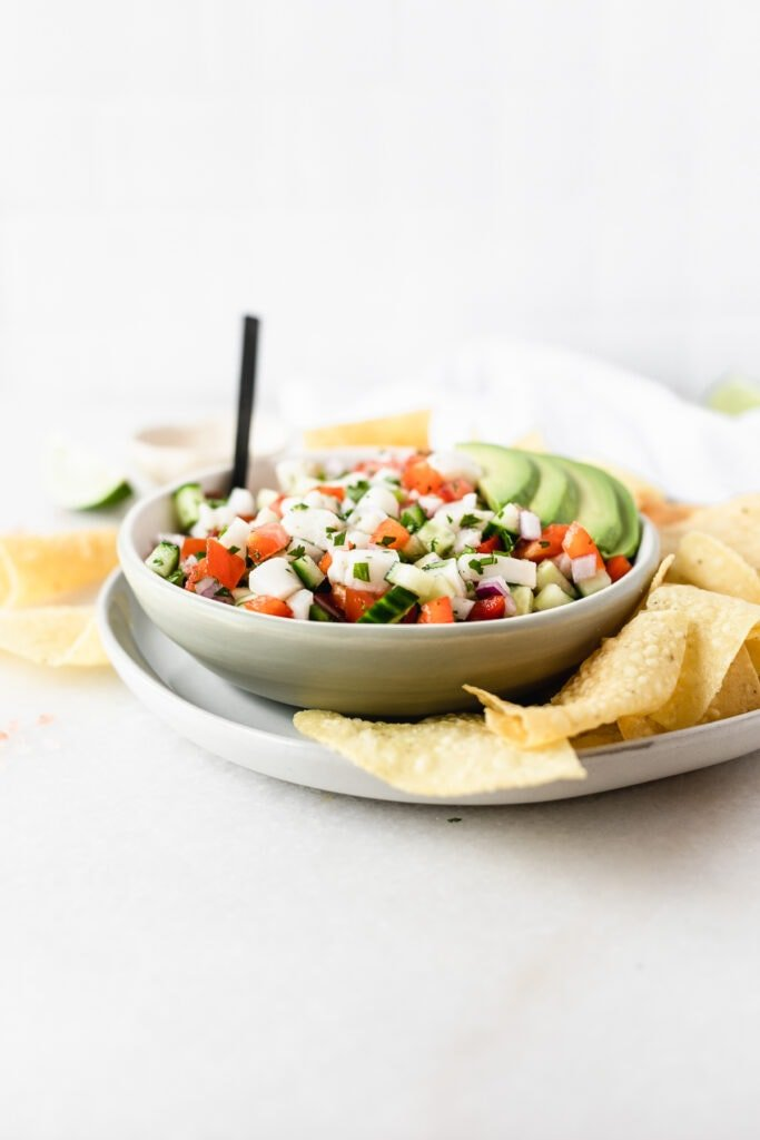 bowl of ceviche with a black spoon in it and sliced avocado on top on a plate with tortilla chips.