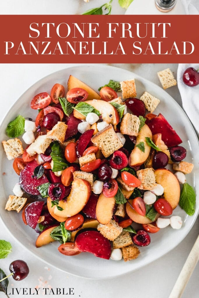 overhead view of stone fruit panzanella salad on a grey plate with text overlay.