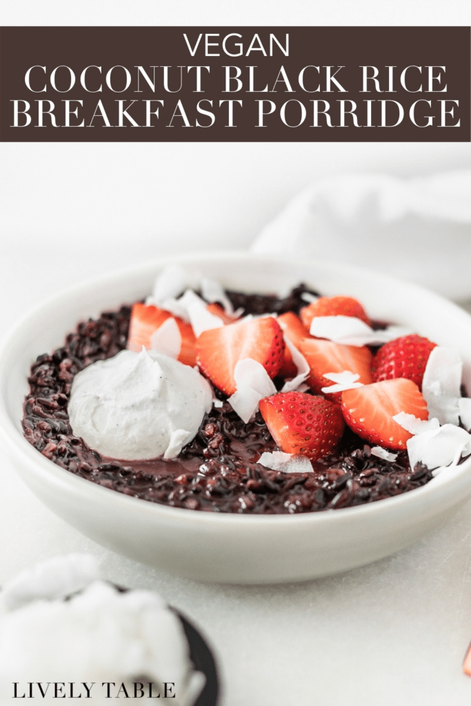 coconut black rice breakfast porridge in a grey bowl topped with strawberries, coconut and coconut whipped cream with text overlay.