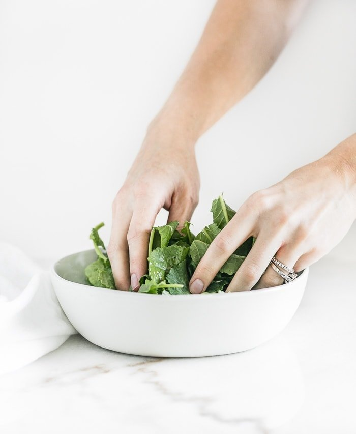 hands messaging kale in a grey bowl.