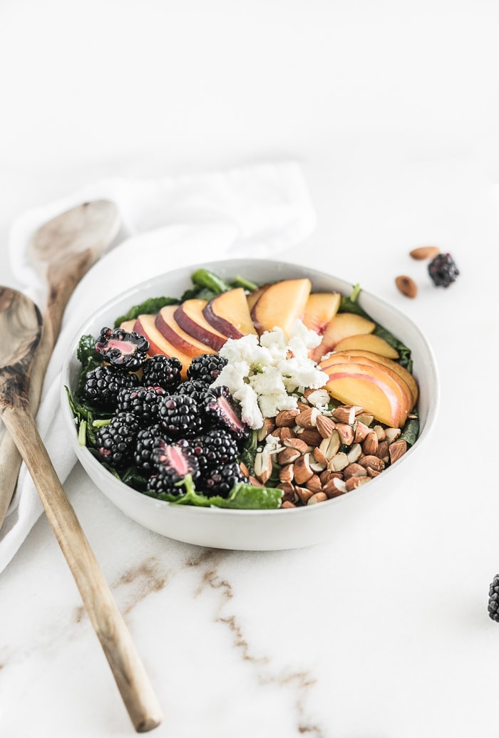 bowl of kale with blackberries, sliced peaches, goat cheese and almonds arranged on top.