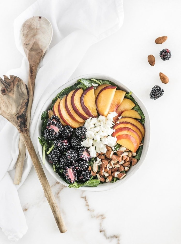kale with blackberries, sliced peaches, almonds, and goat cheese arranged on top with wooden spoons next to the bowl.