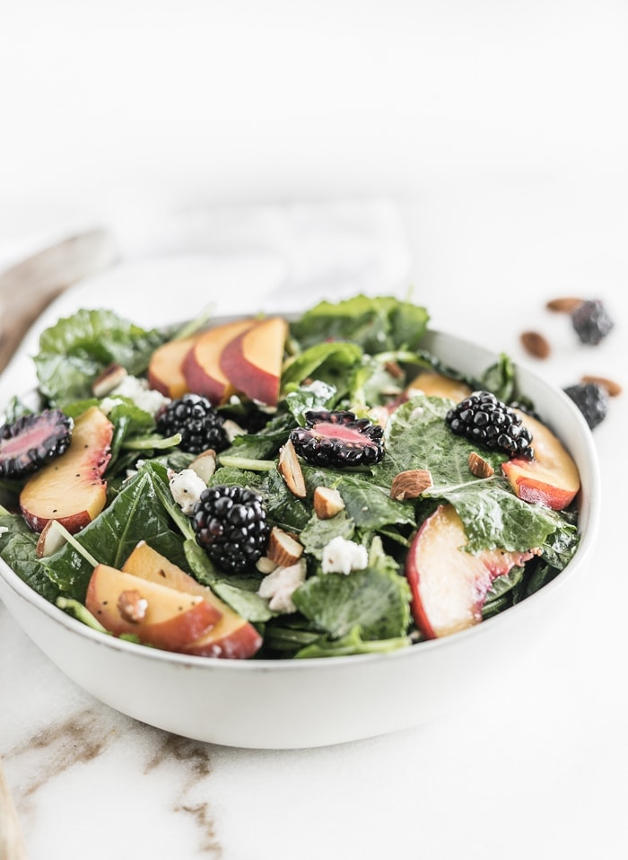 This delicious Blackberry Peach Kale Salad is a great way to eat summer fruit! With toasted almonds, goat cheese, mint and a lemon poppy seed vinaigrette, it's a perfect light lunch or side dish! (#glutenfree, #vegetarian) | #kalesalad #summersalad | via livelytable.com