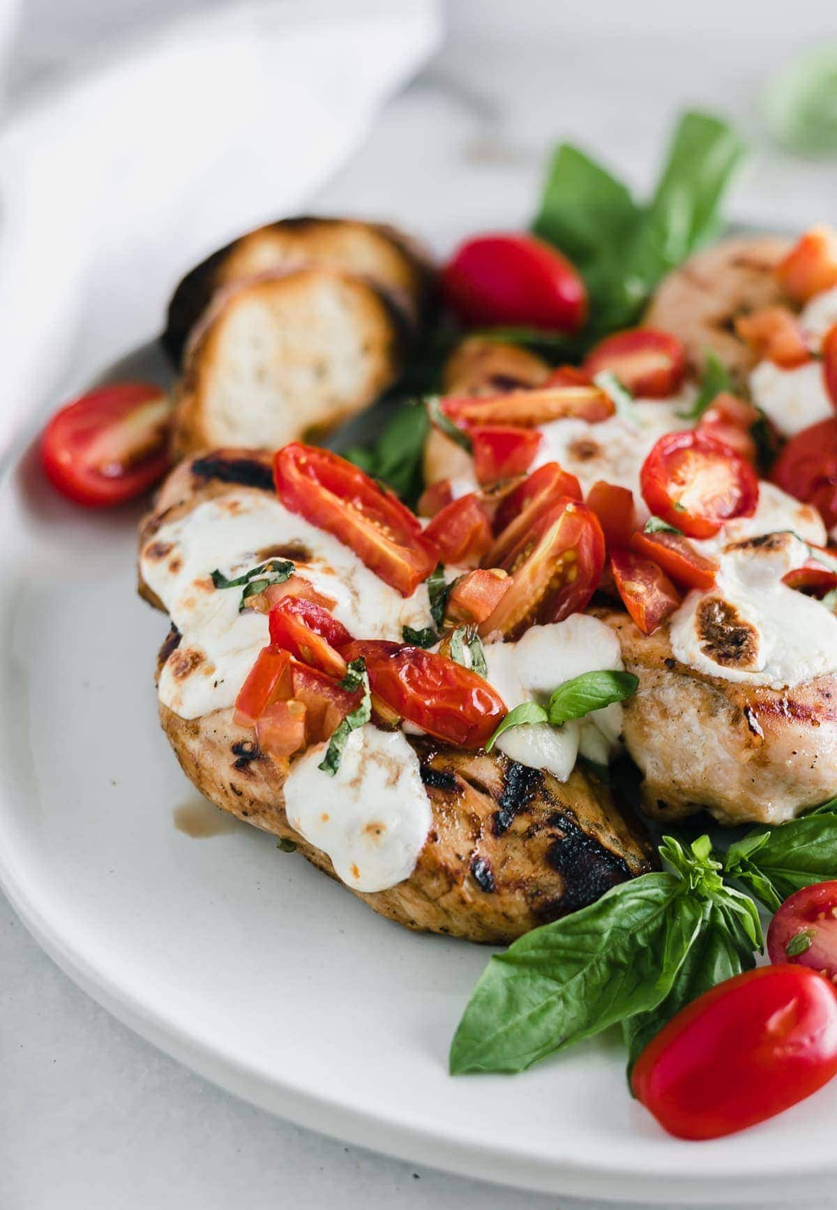 3 Tomato basil bruschetta Chicken breasts on a round cutting board with basil leaves.