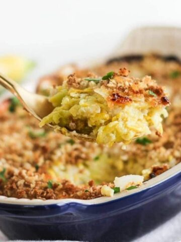 gold spoon lifting cheesy summer squash casserole out of a blue baking dish.