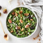 overhead view of fig arugula salad with a gold spoon of balsamic dressing beside it.