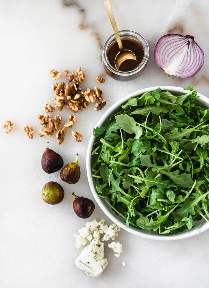 overhead view of ingredients needed to make fig arugula salad on a white marble background.