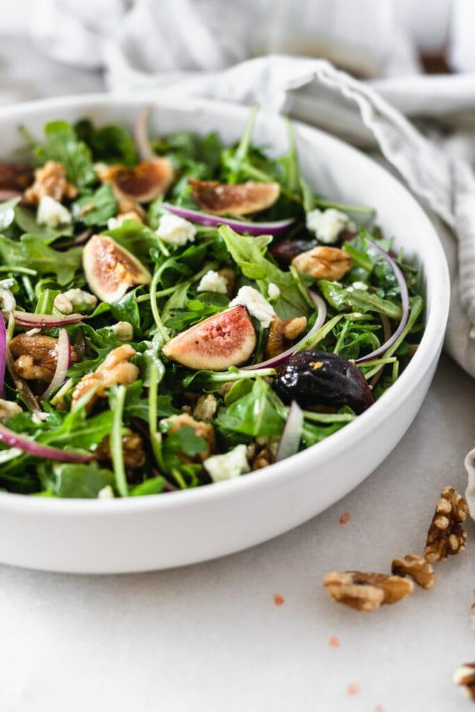 closeup of fig arugula salad in a white bowl.